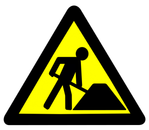 Symbol for work in progress. Yellow triangle sign of a person shoveling the road.
